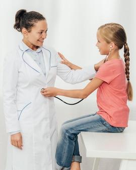 Coup moyen jolie fille vérifiant le médecin