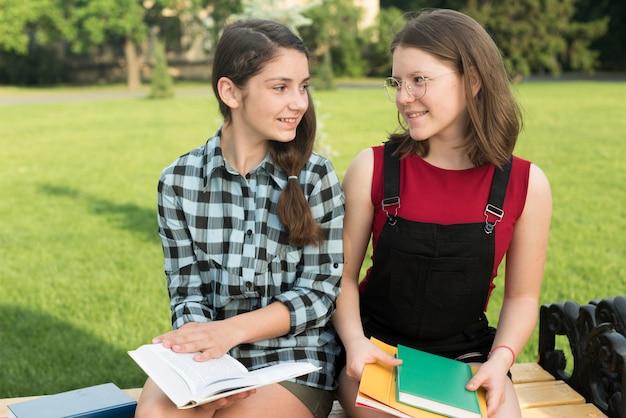 Coup moyen de lycéennes assis sur un banc