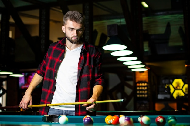 Coup moyen mec avec queue de billard regardant à la table