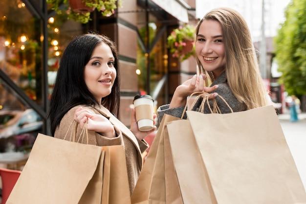 Coup moyen meilleurs amis tenant des sacs à l'extérieur