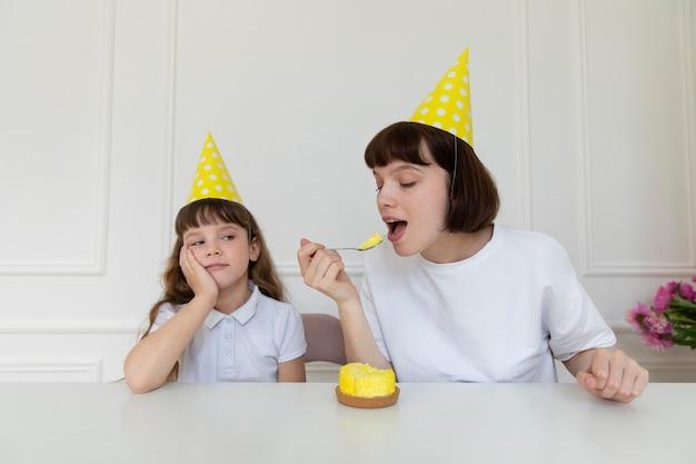 Coup moyen mère mangeant un petit gâteau