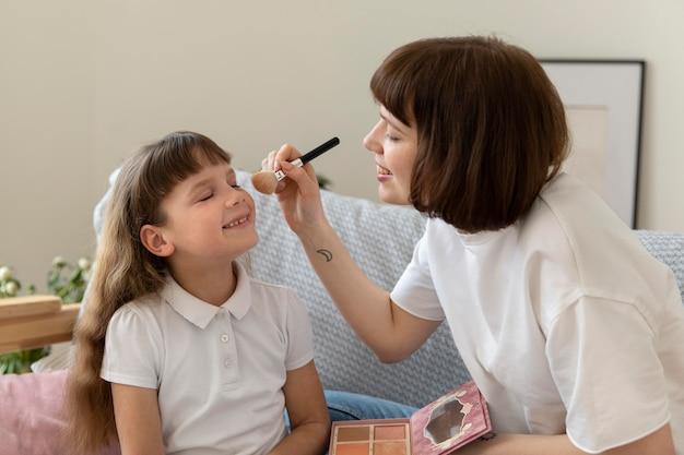 Coup moyen mère tenant un pinceau de maquillage