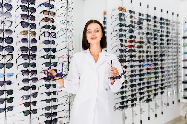 Coup moyen d'opticien tenant des paires de lunettes de soleil