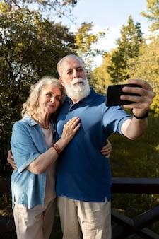 Coup moyen senior couple prenant selfie