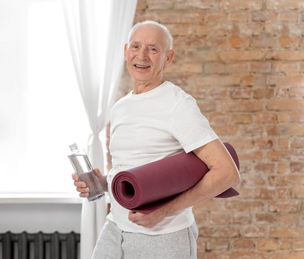 Coup moyen senior man holding tapis de yoga