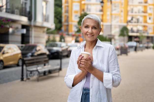 Coup moyen senior woman holding coffee cup
