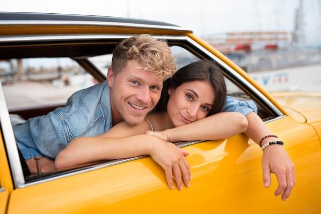 Coup moyen smiley couple à l'intérieur de la voiture