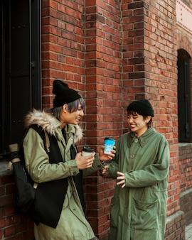 Coup moyen smiley couple tenant des tasses à café
