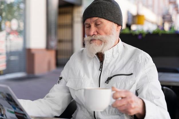 Coup moyen vieil homme tenant une tasse