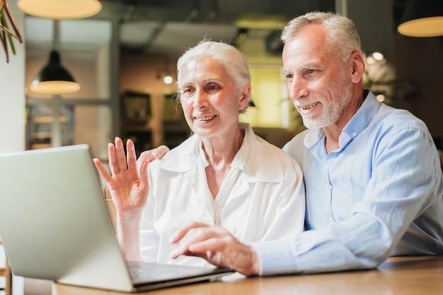 Coup moyen vieille femme agitant à l'ordinateur portable