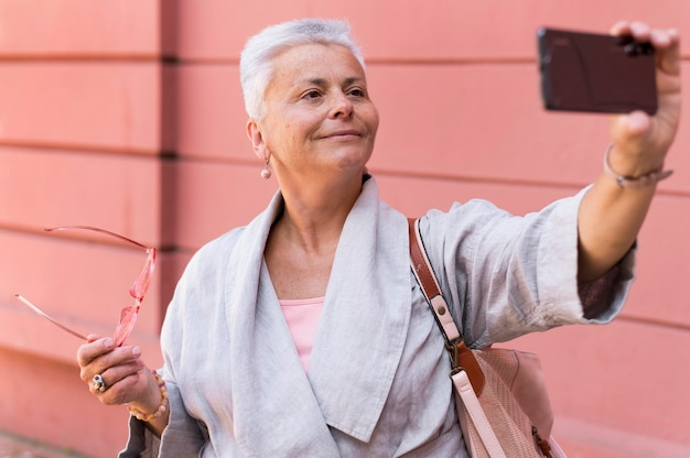 Coup moyen vieille femme prenant selfie