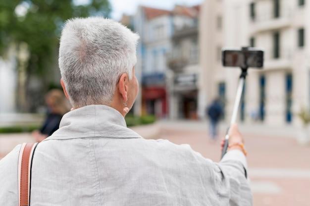 Coup moyen vieille femme tenant un bâton de selfie