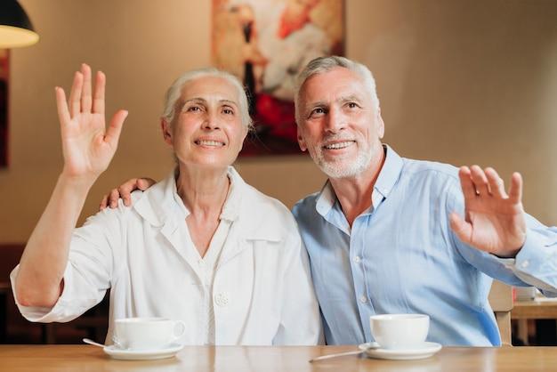 Coup moyen vieux couple faisant signe à quelqu'un