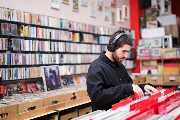 Coup moyen vue de côté du jeune homme à la recherche de vinyles en magasin