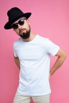 Coup de photo verticale de beau jeune homme brune avec barbe portant un t-shirt blanc décontracté pour maquette de chapeau noir et lunettes de soleil élégantes isolées sur le mur de fond rose regardant la caméra.