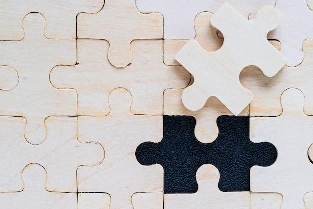 Coup de pièces de puzzle en bois sur fond noir, concept d'entreprise