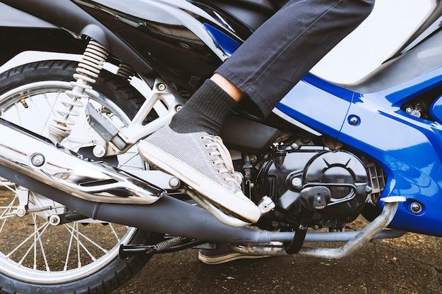 Coup de pied pour commencer le stationnement de moto dans la ruelle avec le vieux fond de mur de briques