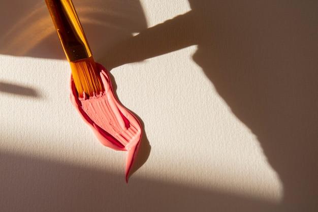 Coup de pinceau avec de la peinture rose sur papier blanc
