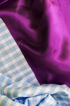 Coup plein cadre de textile à motif uni sur un tissu rose lisse