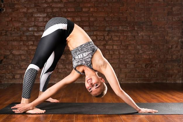 Coup plein femme faisant du yoga à la maison