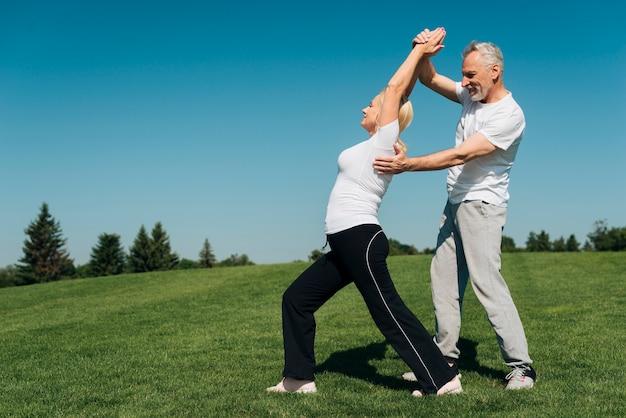 Coup plein homme aidant une femme à redresser son dos