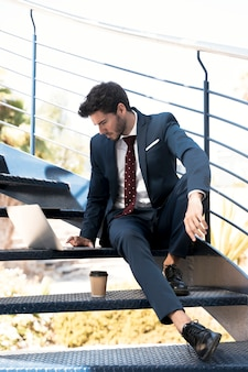 Coup plein homme en costume travaillant dans les escaliers