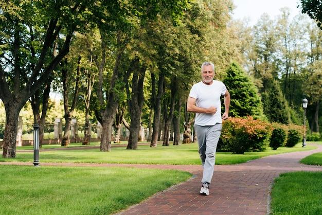 Coup plein vieil homme qui court dans la nature
