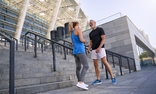 Coup de pleine longueur d'un beau couple sportif d'âge moyen homme et femme en tenue de sport souriant tout en
