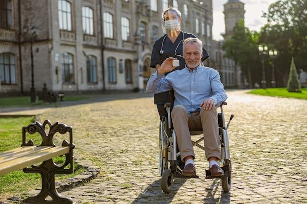 Coup de pleine longueur d'un homme âgé heureux en train de récupérer un patient tenant un pot de crème souriant à la caméra sur un