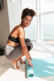 Coup de pleine longueur de jeune femme joyeuse enroulant un tapis après la formation