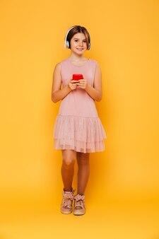 Coup de pleine longueur de jolie fille à l'aide d'écouteurs et smartphone isolé