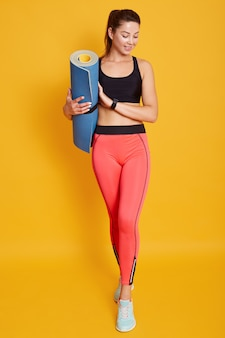 Coup de pleine longueur de jolie jeune femme avec un tapis de yoga, se dresse sur fond de studio jaune avec un espace de copie, regarde vers le bas, une adorable dame habille des vêtements de sport élégants. concept de mode de vie sain.