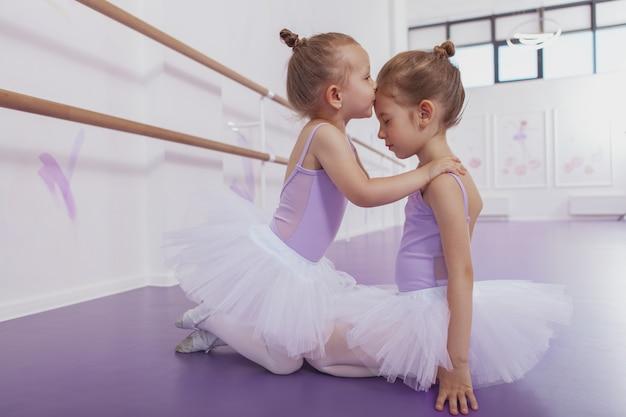 Coup de pleine longueur de jolie petite fille ballerine en jupe tutu embrassant sa sœur aînée sur le front