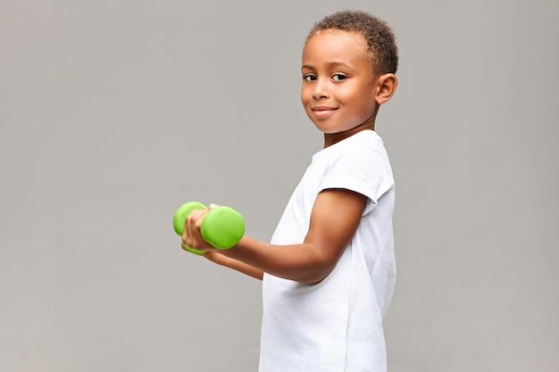 Coup de profil isolé de beau garçon africain joyeux posant au mur blanc gris à l'aide d'un équipement de fitness, tenant un haltère vert, renforcement des muscles du bras, regardant avec un sourire heureux