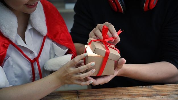 Coup recadré couple doux ouvrant des cadeaux de noël.