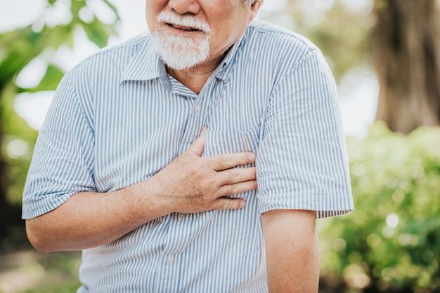 Coup recadrée d'un homme âgé tenant sa poitrine et ressentant une douleur causée par une crise cardiaque