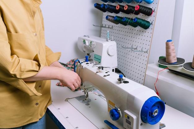 Coup sans visage de femme ajustant la machine à coudre avant de travailler dans un atelier de couture