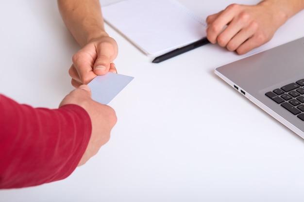 Coup sans visage d'homme d'affaires donnant une carte de visite à un partenaire, assis à un bureau blanc avec un ordinateur portable, les gens négocient au bureau