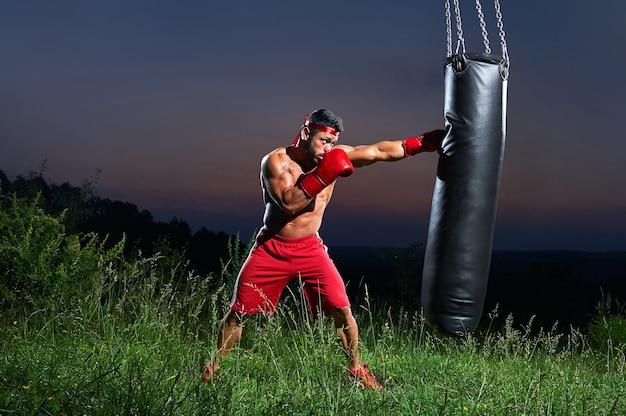 Coup saturé d'un boxeur masculin s'entraînant avec un sac de sable