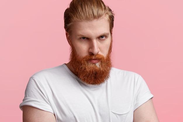Coup de sérieux jeune homme aux cheveux roux avec une longue barbe de gingembre, expression réservée, regarde avec confiance