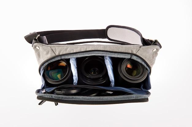 Coup de studio isolé en gros plan d'un petit photographe moderne à la mode gris sac de taille antichoc compartiment souple sac banane transporter objectif appareil photo reflex numérique et smartphone à l'intérieur sur fond blanc.