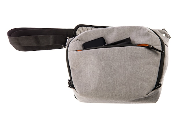 Coup de studio isolé en gros plan d'un petit photographe moderne à la mode gris sac de taille antichoc compartiment souple sac banane transporter smartphone et portefeuille dans la poche avant zippée sur fond blanc.