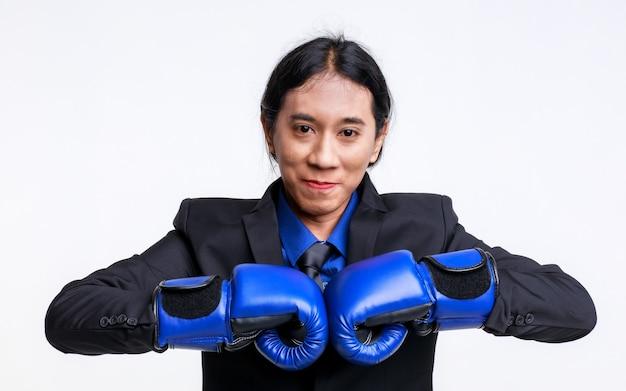 Coup de studio isolé d'un stress fou asiatique déprimant un homme d'affaires fou en costume formel noir debout portant un gant de boxe bleu frappant et blessant son propre visage en criant de douleur sur fond blanc.