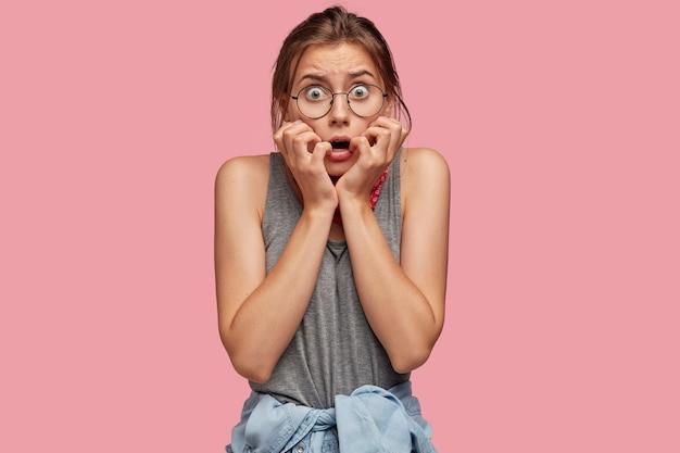 Coup de taille de belle petite amie caucasienne regarde la caméra avec une expression effrayée, garde les mains près de la bouche