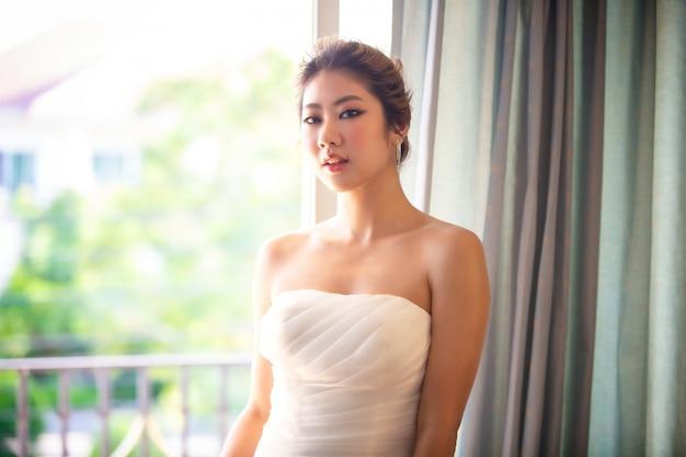 Coup de tête de belle jolie femme souriante en robe de mariée blanche avec une coiffure de cheveux de mariée.