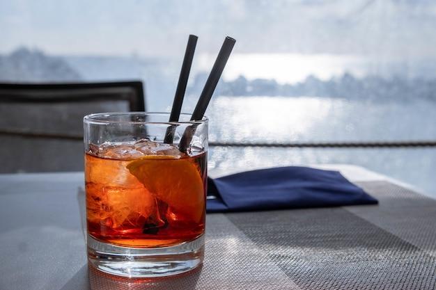 Coup de thé glacé savoureux avec de la glace et une tranche de citron dans un verre avec deux pailles