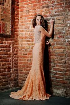 Coup toute la longueur de la fille modèle à la mode à la robe de soirée pêche avec mur de briques.