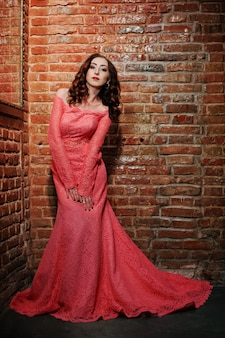 Coup toute la longueur de la fille modèle à la mode à la robe de soirée rose avec mur de briques.