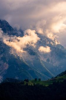 Coup vertical de belles montagnes couvertes de nuages épais et de vallées vertes