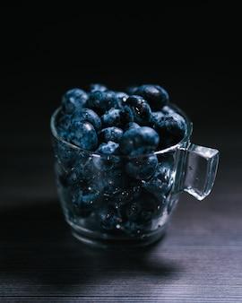 Coup vertical de bleuets dans un verre sur un tableau noir
